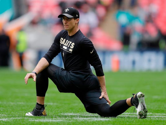 FILE - In this Oct. 1, 2017, file photo, New Orleans Saints quarterback Drew Brees stretches before the team's NFL football game against Miami Dolphins at Wembley Stadium in London. Brees has filed suit accusing a California businessman of cheating him out of $9 million through jewelry purchases. (AP Photo/Matt Dunham, File)