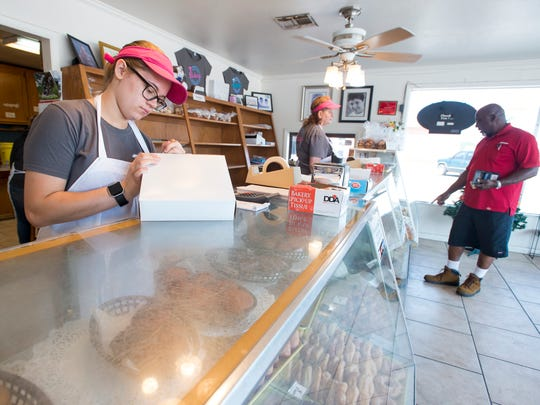 """Emily Reagin, left, prepares a customer's order at the Milton Quality Bakery in Milton on Monday, May 14, 2018.  The bakery, which is competing in the """"Sweetest Bakery in America Contest"""", currently has the second most votes in the state of Florida."""