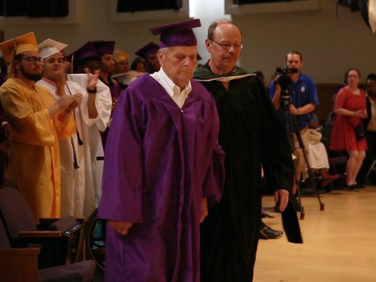Henry Ross, 93 of Hilton, guided by his nephew, walks on to the East High School stage to receive his honorary diploma. A World War II veteran, he left school after his junior year to work and was later drafted.