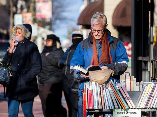 Mike Migliore looks at books on a discount rack outside the Ninth Street Book Store on Market Street in Wilmington on Friday afternoon.