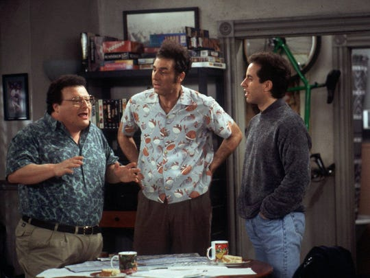 "Newman (Wayne Knight), left,  and Kramer (Michael Richards), center, explain their new idea of bringing a rickshaw business to New York City to Jerry (Jerry Seinfeld) in this scene from a 1998 episode of NBC's hit sitcom ""Seinfeld."""