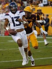 Arizona backup quarterback Brandon Dawkins runs for