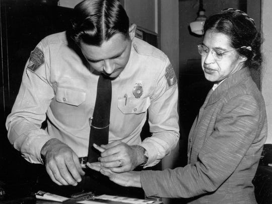 FILE - In this Feb. 22, 1956, file photo, Rosa Parks is fingerprinted by police Lt. D.H. Lackey in Montgomery, Ala., after refusing to give up her seat on a bus for a white passenger on Dec. 1, 1955. Yellowing court records from the arrests of Rosa Parks, Martin Luther King Jr. and others at the dawn of the modern civil rights era are being preserved and digitized after being discovered, folded and wrapped in rubber bands, in a courthouse box. (AP Photo/Gene Herrick, File)