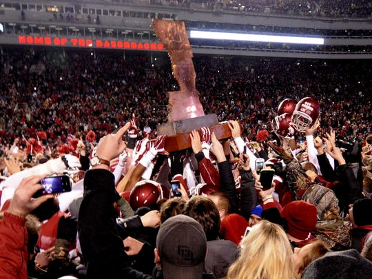 "Arkansas players and fans celebrate with ""The Golden Boot"" trophy after Arkansas defeated LSU 17-10 in Fayetteville, Arkansas, Saturday night. The win snapped a 17-game SEC losing streak for the Razorbacks."