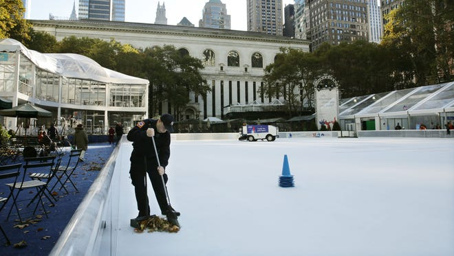 Debris is swept from the ice skating rink at Bryant Park in New York on Sunday.