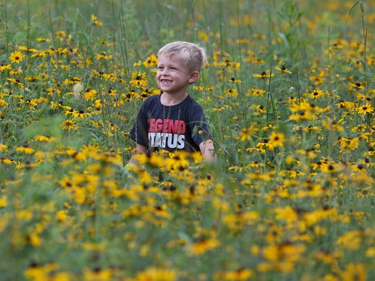Jake Savage, 6, on Thursday smiles for a snapshot taken by his mother,  Shue-Medill Middle School principal Michele Savage, as he and other school community members work on the blossoming Learning Meadow being created in a former grassy field at the school.