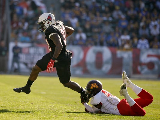National team running back Jahwan Edwards, left, of Ball State, carries the ball against American team defensive back Cedric Thompson, of Minnesota, during the first half of the NFLPA Collegiate Bowl football game Saturday, Jan. 17, 2015, in Carson, Calif. (AP Photo/Jae C. Hong)
