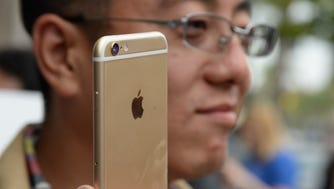 """(FILES) This September 19, 2014 file photo shows Tony Zhan as he checks out his new  iPhone 6 Plus outside the Apple store in Pasadena, California. Global smartphone sales grew at a healthy pace in the third quarter, boosted by low-cost handsets in emerging markets, industry research showed on October 30, 2014. The research firm IDC said global smartphone shipments jumped 25.2 percent from a year earlier to 327.6 million in the quarter, and were up 8.7 percent over the second quarter. """"Despite rumors of a slowing market, smartphone shipments continue to see record-setting volumes,"""" said IDC's Ryan Reith. """"We've finally reached a point where most developed markets are experiencing single-digit growth, while emerging markets are still growing at more than 30 percent collectively.  AFP PHOTO / ROBYN BECKROBYN BECK/AFP/Getty Images ORIG FILE ID: 534880212"""