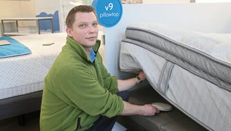 Verlo employee Adam Terasek places a SmartWake sensor - a device that Verlo says will wake a person at the optimal time - under a pillowtop mattress at the Verlo store at 1100 W. Burleigh St., in Wauwatosa's Mayfair Collection shopping center.
