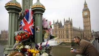 Flowers are left on Westminster Bridge by the Houses of Parliament in memory of those who died in last week's terror attack.