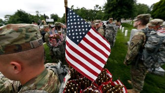 """Soldiers of the 3d U.S. Infantry Regiment (The Old Guard) arrive to place flags at headstones for """"Flags In,"""" at Arlington National Cemetery in Arlington, Va."""