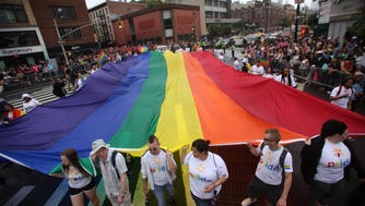 A large rainbow flag is carried at the 2015 Gay Pride parade in Manhattan.