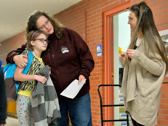 Caitlin White, a sixth grader at Lewis and Clark Elementary School, meets her mom Wendy in the hallway after school as her Family Support Advisor Leah Comisso-Macato recently.
