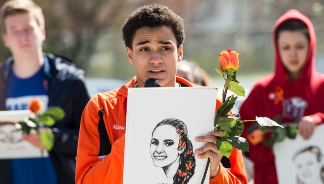 """Malcolm Ellis, a junior at Hanover High School, reads the biography of Alyssa Alhadeff, a 14-year-old student who was one of 17 people killed in the Parkland school shooting in February. Ellis and around 50 other Hanover High School students chose to spend their """"flex"""" period Friday, which was National School Walkout day, to remember the Parkland victims and speak out against gun violence."""