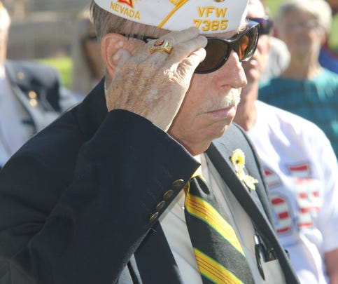 Retired Navy Hospital Chief Corpsman Jim Brown, Mesquite veterans service officer, salutes at Memorial Day ceremony.