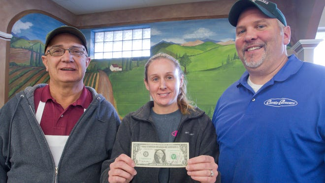 Longtime Curtis Grocery employee Larry Schmid, left, gave Kate Curtis the dollar she holds, inscribed with Larry's phone number as she left for California in 1999 to be married to her now ex, saying if she needed anything, to call. She was then an employee with Larry at the grocery story. After that marriage ended, she returned and married Craig Curtis, right, who co-owns the grocery story with his father Ken. Curtis Grocery will close soon.