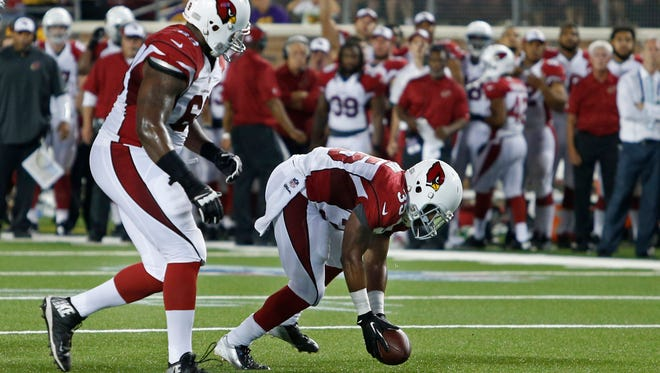 Aug 16, 2014: Cardinals running back Zach Bauman (35) picks up the ball after a fumble and scores a touchdown against the Minnesota Vikings in the fourth quarter at TCF Bank Stadium. The Vikings win 30-28.