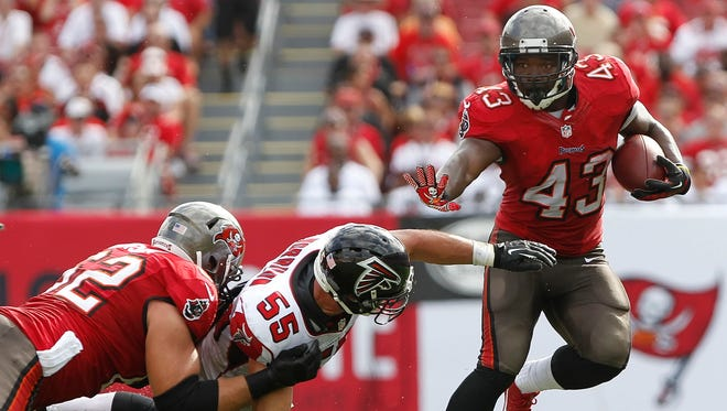 Tampa Bay Buccaneers running back Bobby Rainey (43) stiff arms Atlanta Falcons outside linebacker Paul Worrilow (55) as he runs past him during the first half at Raymond James Stadium.