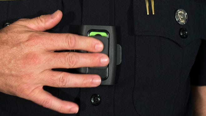 Phoenix police Sgt. Trent Crump demonstrates the department's body cameras.