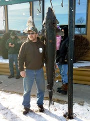 Dan Graham of Alvin, Wis. stands next to a 122.5-pound, 80-inch sturgeon he speared on Sunday.