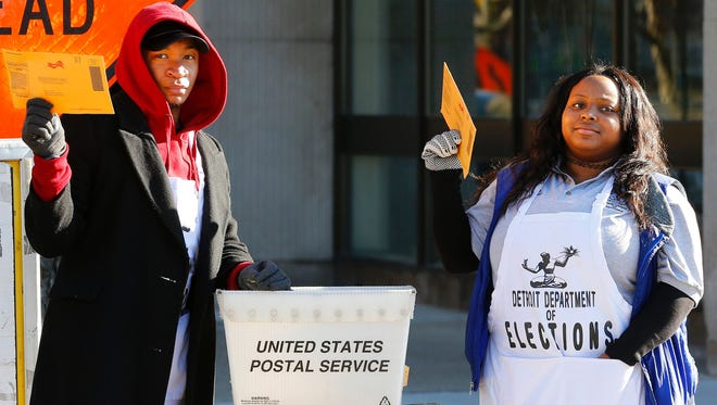 Marquis Simpson (L) and LaSean Madden collect absentee ballots outside the Detroit Elections Department on November 4, 2016 in  Detroit, Michigan.  White House frontrunner Hillary Clinton and Republican insurgent Donald Trump launched a final blitz to win votes in key battleground states Friday, slogging toward the end of America's divisive presidential campaign.