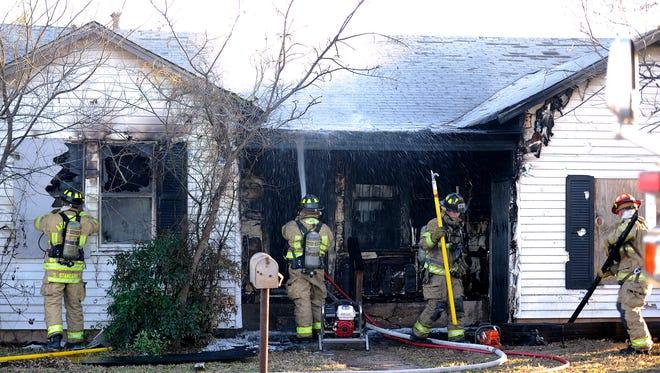 Abilene firefighters spray down hotspots at a house fire on Lowden Street on Thursday, Jan. 26, 2017.