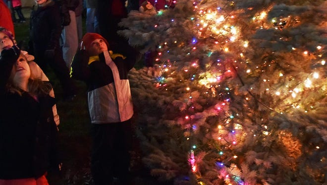"The eyes of a few youngsters follow the lights of the Sturgeon Bay Christmas tree all the way to the top after the tree was lit for the first time last year outside the Nicolet Bank Clock Tower on North Third Avenue to kick off the city's ""Christmas By the Bay."""