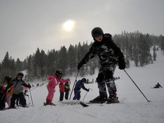Kids from the Junior Ski Program trek up a hill at Sky Tavern in 2010.