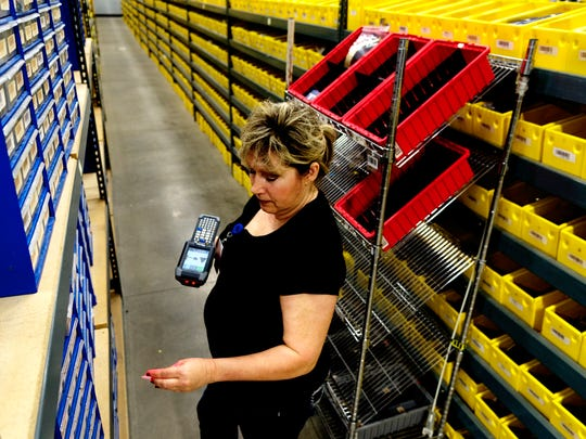 Fulfillment agent Angelia Clabaugh looks for merchandise among rows of shelves in the new addition to the Jewelry Television Headquarters on Thursday, January 12, 2017. JTV is seeing about 15% in sales growth at a time when the jewelry market is down. The company is also finishing up a three-phase building expansion, including an automation system and more inventory space.