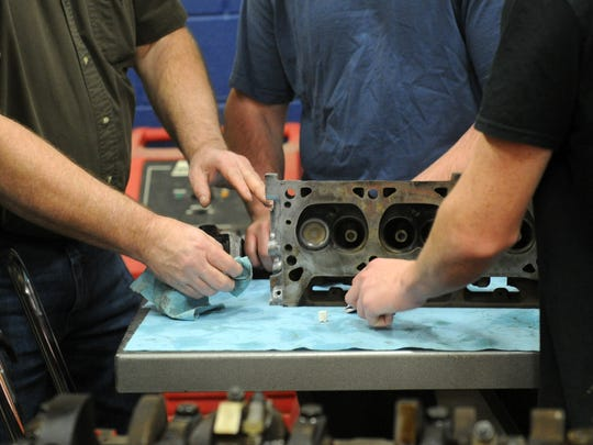 Students work on a car engine.