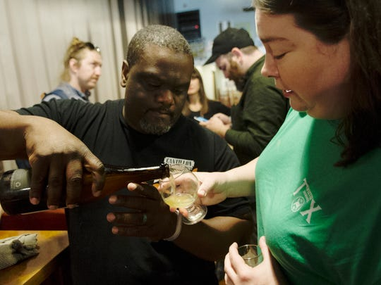 Willie Robinson pours Joy Harris some Side Project Grisette during a beer bottle share at Suttree's in Knoxville, Tennessee on Saturday, March 25, 2017. A crowd of around 100 people shared beers from throughout the world including craft beers and speciality beers.