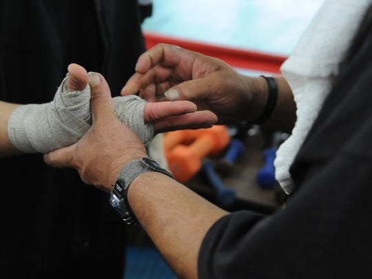 Medrano (right) tapes up one of the boxer's hands before they spar in the ring.