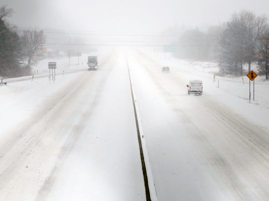 Vehicles slowly drive near the Exit 49 overpass on