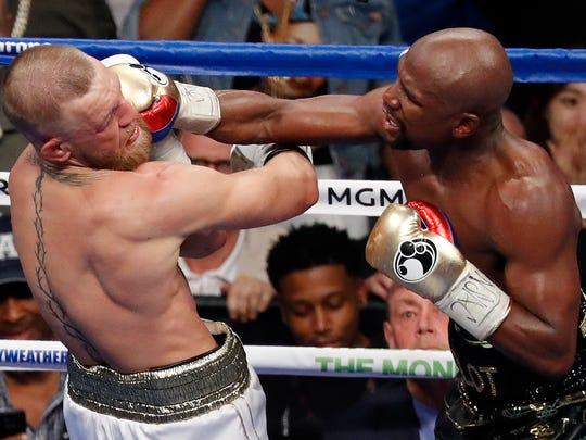 FILE - In this Aug. 26, 2017, file photo, Floyd Mayweather Jr. hits Conor McGregor in a super welterweight boxing match in Las Vegas. The AP reported on Sept. 1, 2017, that a story claiming a boxing promoter connected to the fight was found shot dead in Washington, D.C. is a hoax.