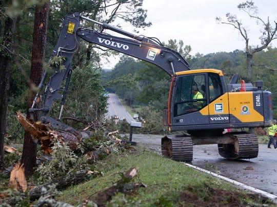 Crews work to remove fallen trees and power lines after a storm earlier this summer. Irma is expected to bring more damage to the area.