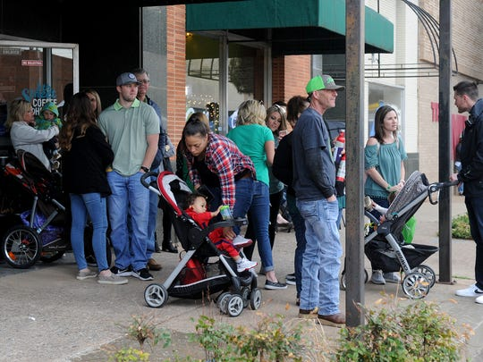 Wichitans take shelter from the rain at the St. Patrick's Day Street Festival downtown on Indiana and Eighth streets.