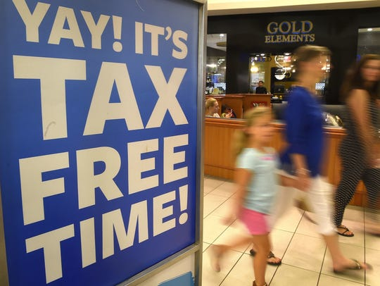 Customers pass by signs advertising a tax-free shopping
