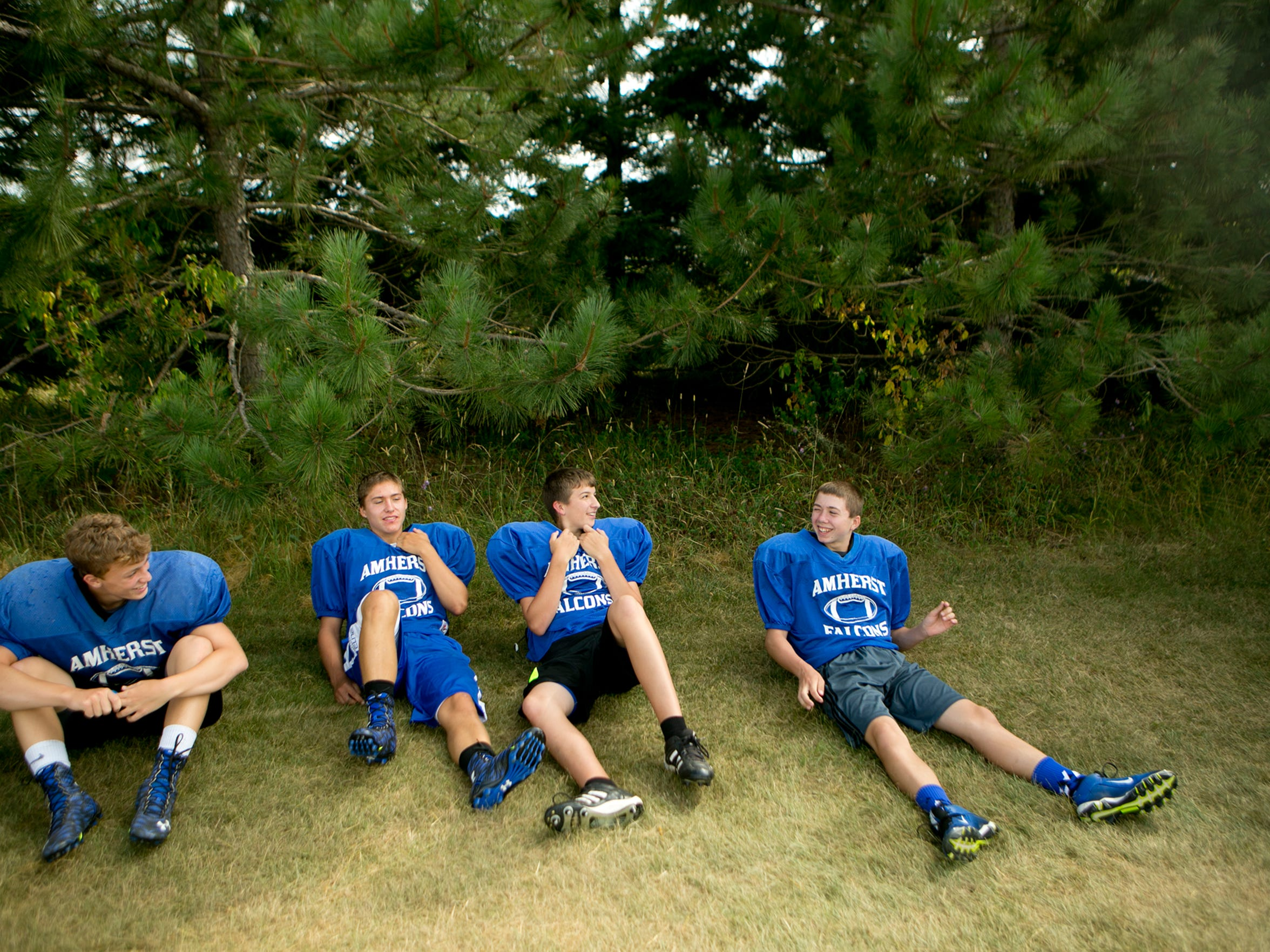 Amherst football players sit in the shade before Amherst football practice starts, Thursday, Aug. 6, 2015.