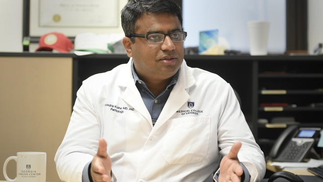 FILE - Director of the Georgia Esoteric & Molecular Laboratory (GEM) Dr. Ravindra Kohle talks about testing saliva for coronavirus at the GEM lab at the Medical College of Georgia in Augusta, Ga., in Augusta, Ga., Wednesday morning May 27, 2020.