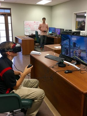 University of Louisiana of Lafayette students Matt Prilliman (front) and Kary Ritter (back) demonstrate a new virtual reality application they created that allows users to take an interactive tour of the Cleco Alternative Energy facility in Crowley and learn about engineering in the process. Ritter can be seen both in the background and on the computer screen.
