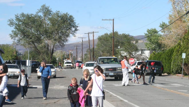 Crossing guards stop traffic to let children cross the street in the crosswalk in front of Fernley Elementary School as others walk along the side of the road on Hardie Lane.
