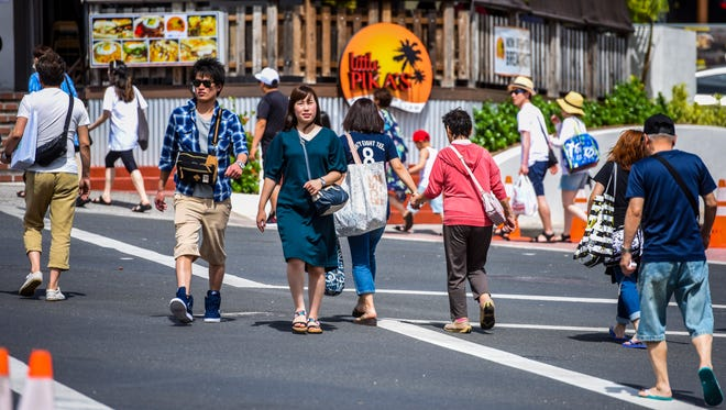In this April 25 file photo, pedestrians make their way across San Vitores Road in Tumon. Increasing the hotel occupancy tax would hurt Guam's tourism industry.