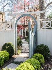 A manicured path leads through a charming gate to the arbor-covered dining area.