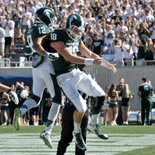 Connor Cook (18) celebrates his first quarter touchdown with teammate R.J. Shelton (12).