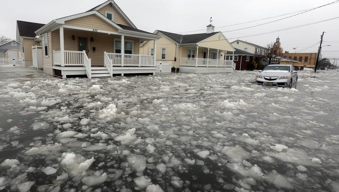 Water and ice floods 12th Ave in North Wildwood, N.J., at the height the storm on Saturday, Jan. 23, 2016. A winter storm created near record high tides along the Jersey Shore, surpassing the tide of Hurricane Sandy according to North Wildwood city officials. (Dale Gerhard/Press of Atlantic City via AP)