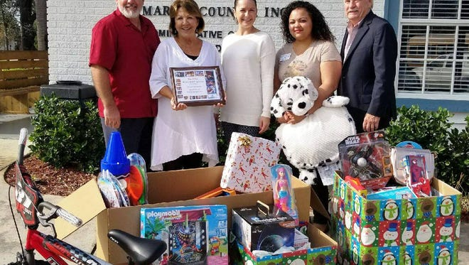 Mike Sancho, left, vice president of operations, Boys & Girls Clubs of Martin County; Sharyl Pratt, Illustrated Properties; Sarah Torres, chief outcomes officer of Boys & Girls Clubs of Martin County; Samantha Melendez, Outcomes administrator, Hobe Sound Boys & Girls Club and Michael Dooley, Illustrated Properties were in the holiday spirit as club members accepted donated gifts from the generous staff at Illustrated Properties.