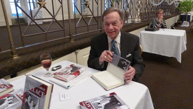 As a special guest, George Wallace, Jr. autographs The Man You Never Knew, the memoir of his father, Governor George Wallace, during the Retired Officers Wives Club's 51st anniversary luncheon.