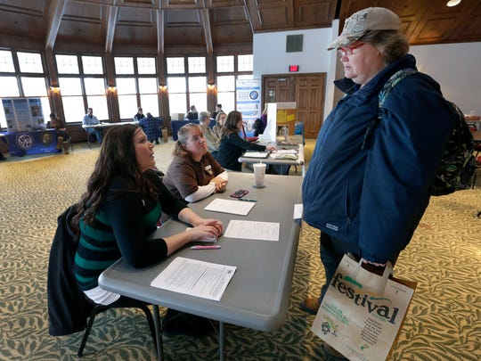 Jeanne Borg (right), of Appleton, inquires about her spot on a waiting list for housing with Jillian Burgess (left) and Kendra Krisher of Housing Partnership on Thursday during the Point-in-Time Resource Picnic at Riverview Gardens in Appleton.