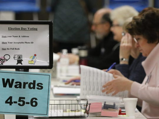 Poll workers check in a steady stream of electors at