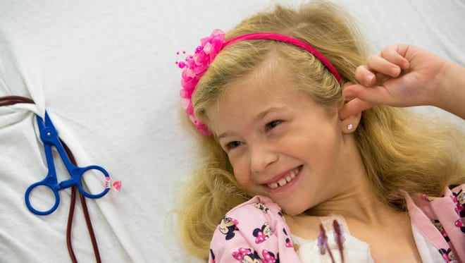 Avery Watts, 7, smiles as she is plugged into a machine that filters her blood, removing the high levels of cholesterol from her body at Nemours/A.I. duPont Hospital for Children.